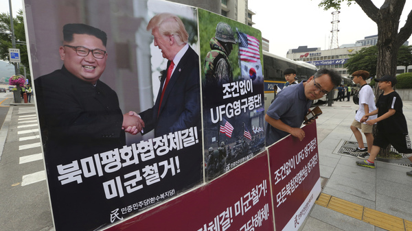A photo of President Trump and North Korean leader Kim Jong Un is on display as a member of People