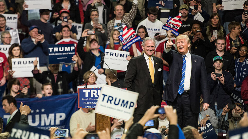 Then-candidate Donald Trump is introduced by then-South Carolina Lt. Gov. Henry McMaster at a campaign rally in Florence, S.C., in 2016. Now Trump is president and McMaster is governor and campaigning for a full term. (Sean Rayford/Getty Images)