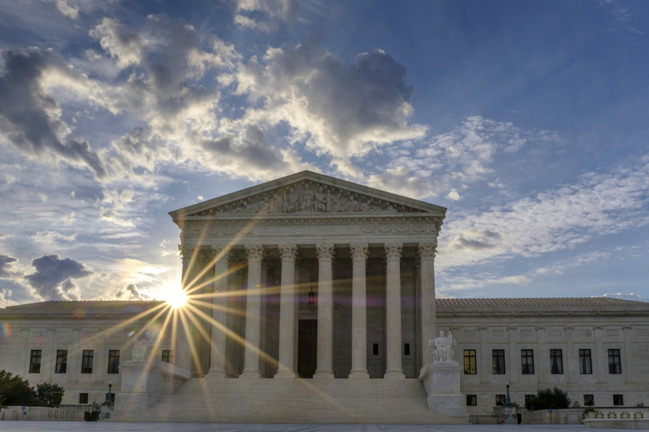 The sun flares in the camera lens as it rises behind the U.S. Supreme Court building in Washington. (J. David Ake/AP)