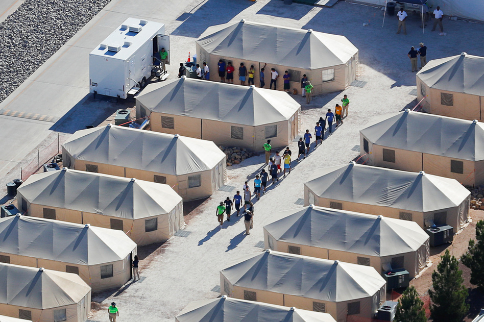 """Migrant children now housed in a tent encampment under the Trump administration's """"zero tolerance"""" policy are shown walking in single file at the facility near the Mexican border in Tornillo, Texas, on June 19. (Mike Blake/Reuters)"""