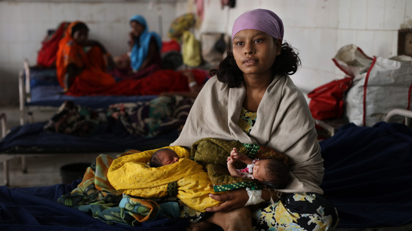 A mother holds her newborn twins at a Sri Krishna Medical College and Hospital, a public health facility in India.