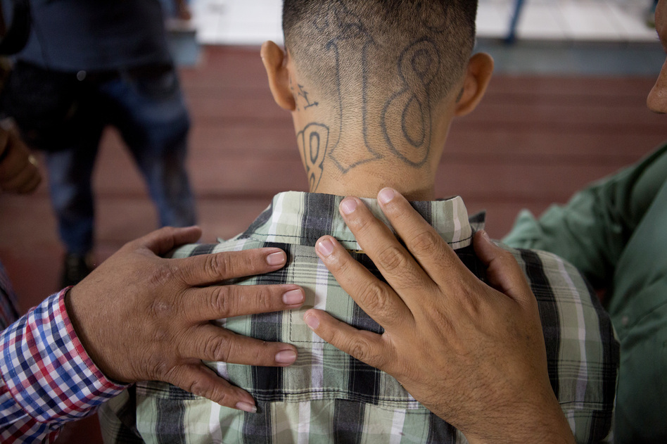 José Rolando Arévalo, a 24-year-old ex-gang member, prays at Eben-ezer church. His head is tattooed with the number 18, a reference to his affiliation with the Barrio 18 gang.