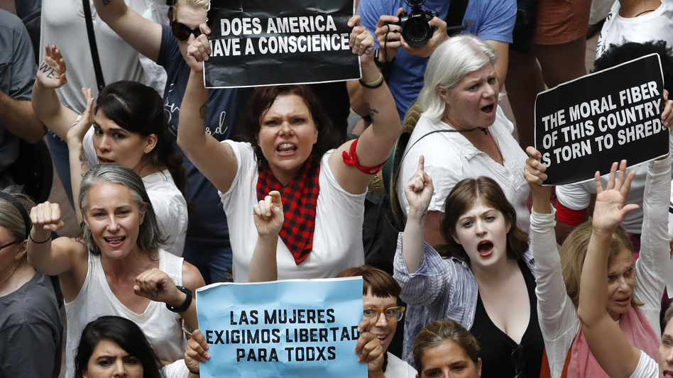 Women hold signs as they protest the separation of immigrant families inside the Hart Senate Office Building on Capitol Hill in Washington. (Jacquelyn Martin/AP)