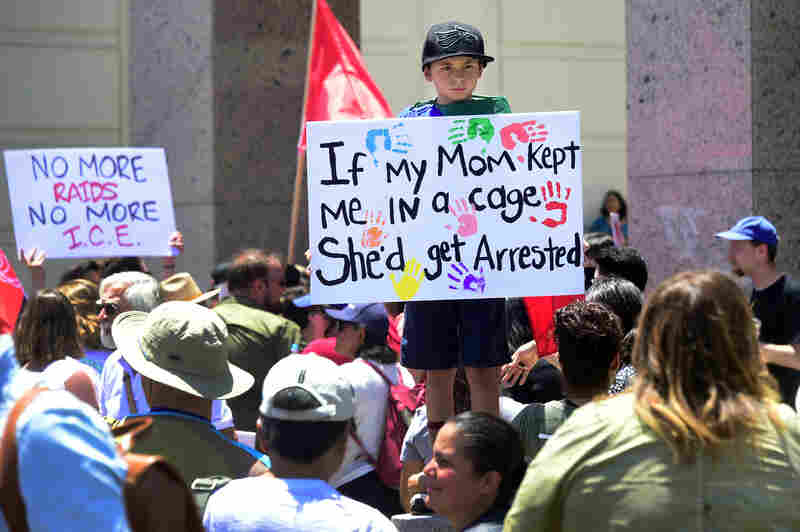 People hold placards during a 'Familes Belong Together' march and rally in Los Angeles, California.