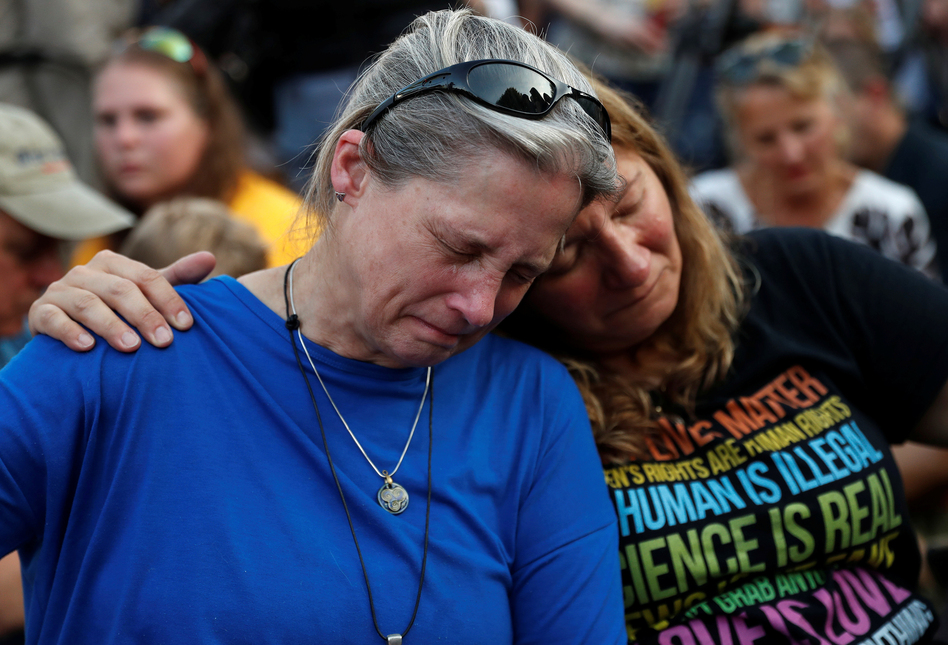 Community members Carol Geithner, left, and Yasemine Jamison take part in a candlelight vigil near the Capital Gazette, the day after a gunman killed five people inside the newspaper's building in Annapolis. (Leah Millis/Reuters)