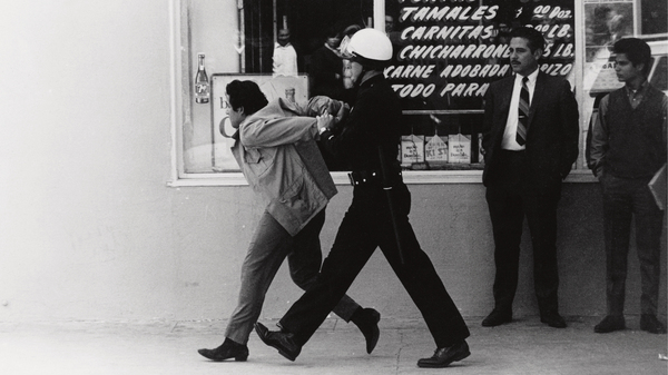 Los Angeles police arrest a Chicano student protester in the neighborhood of Boyle Heights in 1970. This image is seen on the cover to George Rodriguez
