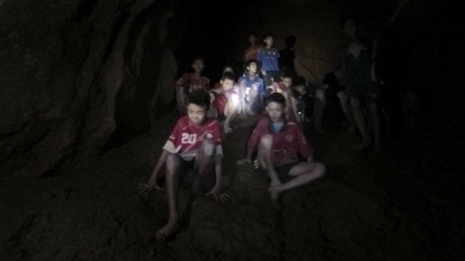 The boys and their soccer coach, seen in partially flooded cave in northern Thailand on Monday. Found after more than a week of searching, they are mostly in stable medical condition and have received high-protein liquid food, officials said Tuesday. (Tham Luang Rescue Operation Center/AP)