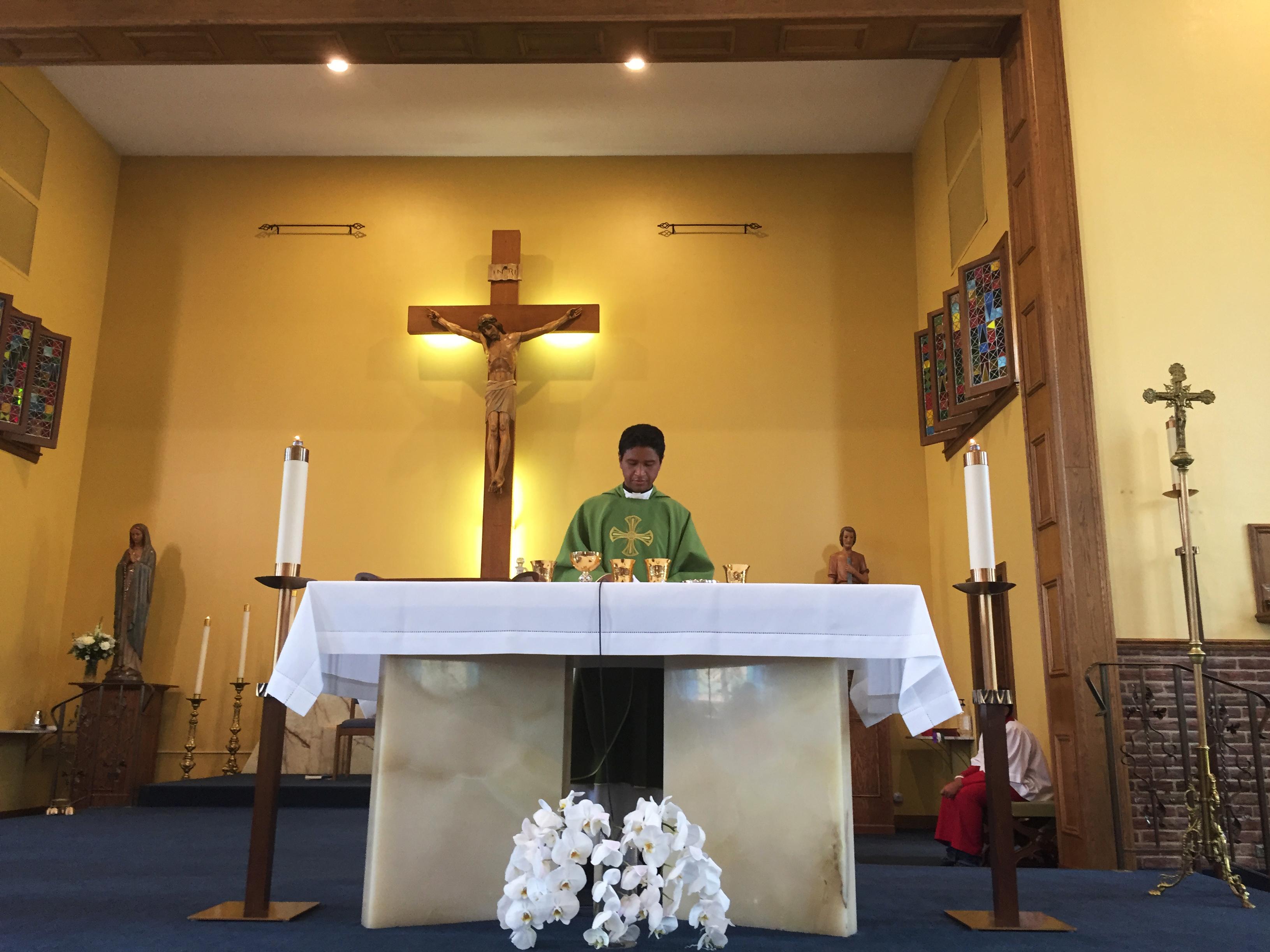 The Rev. Matthew Nathan celebrates a Spanish-language Mass at St. Alexis. (David Schaper/NPR)