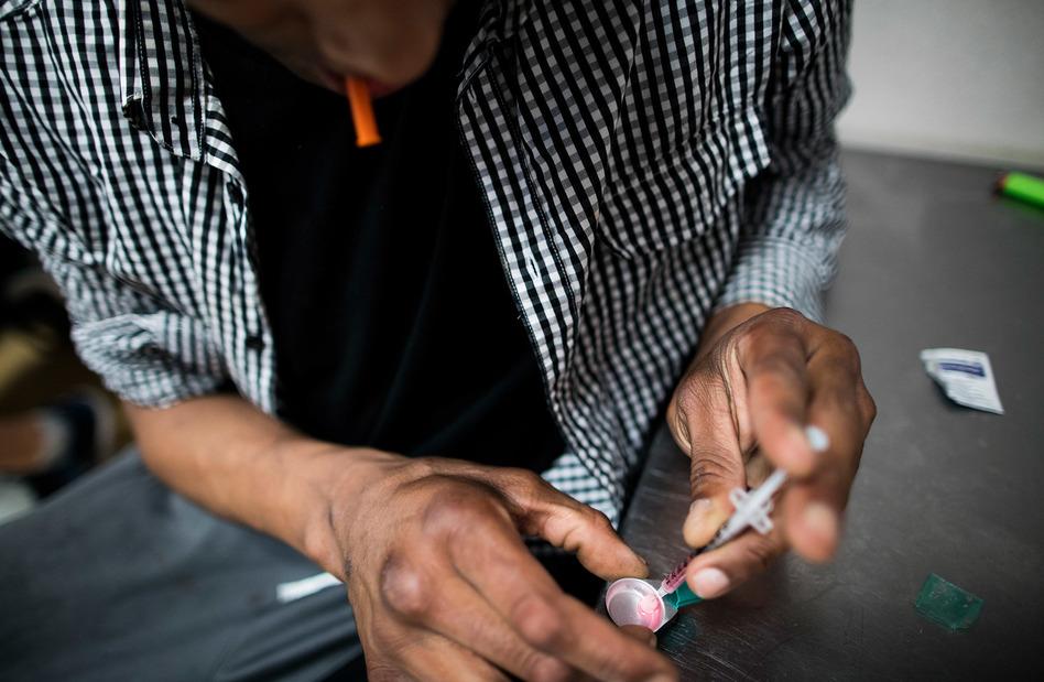 A drug user prepares a hit of heroin inside VANDU's supervised injection room. (Rafal Gerszak for NPR)