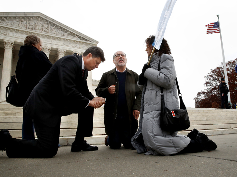 Rev. Brad Wells, left, Rev. Patrick Mahoney and Paula Oas, kneel in prayer in front of the Supreme Court in December as justices hear arguments in the Masterpiece Cakeshop case. (Jacquelyn Martin/AP)