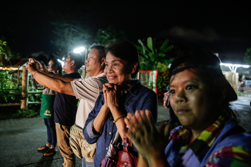 Onlookers watch and cheer as ambulances deliver boys rescued from a cave in northern Thailand to a hospital in Chiang Rai on Sunday.