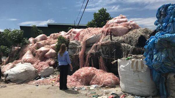 Waste engineer Jenna Jambeck, of the University of Georgia, surveys plastic waste in a southeast Asian village, where it will be recycled to make raw material for more plastic products.  Jambeck advises Asian governments on how to keep plastic trash out of waterways.