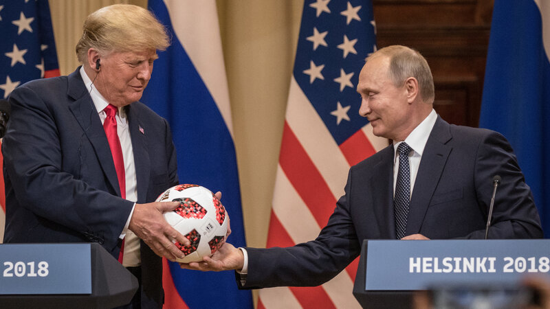 Russian President Vladimir Putin hands President Trump a World Cup soccer ball during a joint news conference after their summit on Monday in Helsinki. (Chris McGrath/Getty Images)