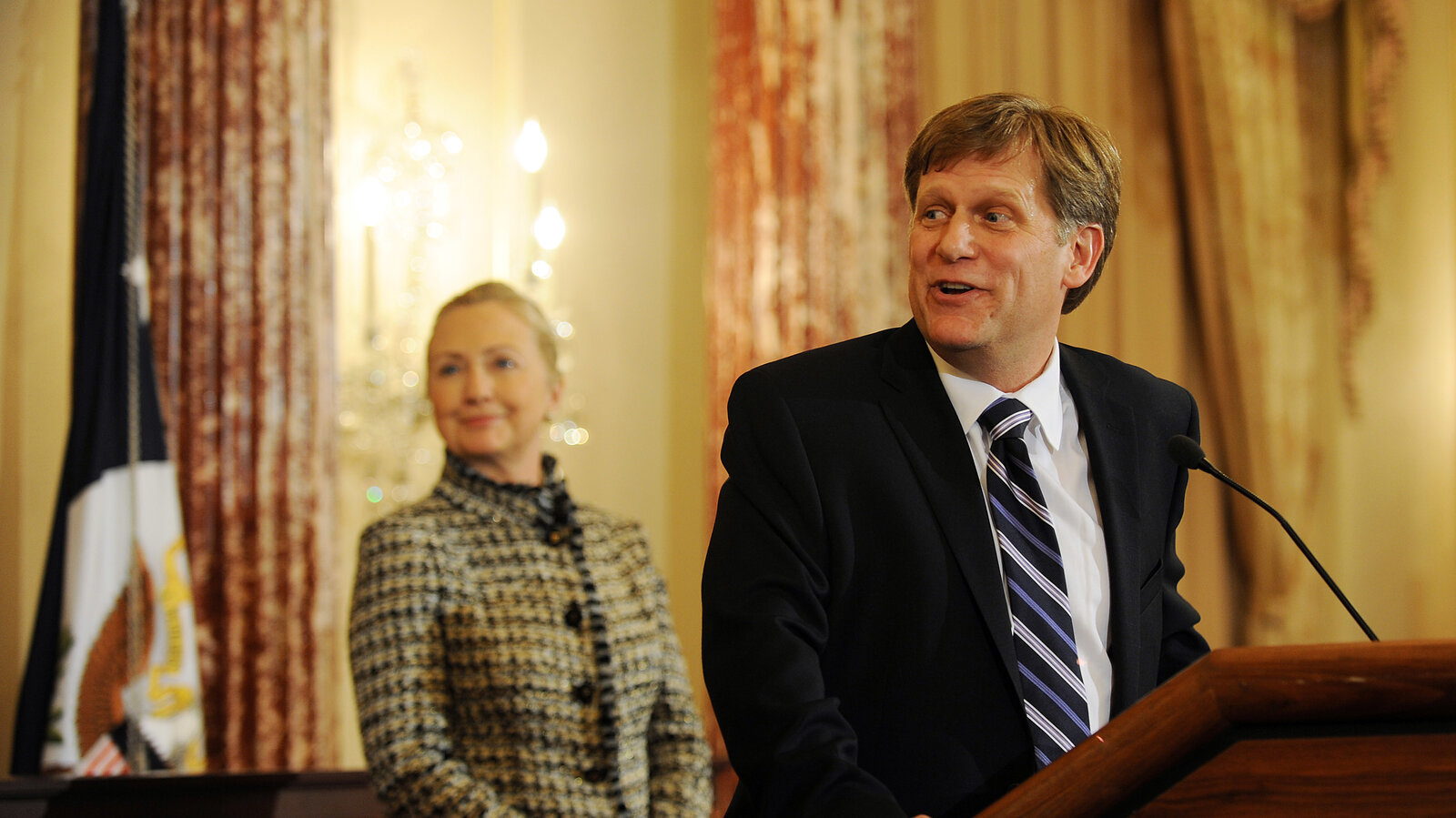 'U.S. Secretary of State Hillary Clinton smiles at a remark made by Ambassador-Designate to Russia Michael McFaul during his swearing-in ceremony at the State Department in 2011. (Astrid Riecken/Getty Images)