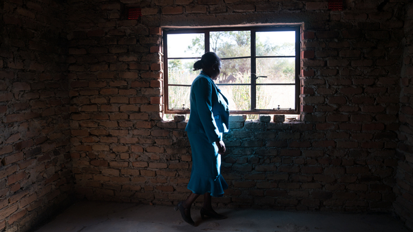 Florence Machinga, a candidate for the opposition MDC party, looks out the window of her house, which was burned down 10  years ago by an angry mob. The incident was one in a wave of violence carried out against MDC supporters in 2008. Machinga is still slowly rebuilding the home.