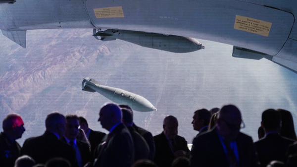 Participants at a global security conference in Moscow in April gather near a big screen showing a Russian warplane unloading its weapons over a target in Syria. Russia became involved in the Syrian civil war in 2015 in support of its ally President Bashar Assad.