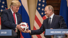 Russian President Vladimir Putin hands President Trump a World Cup soccer ball during a joint news conference after their summit on Monday in Helsinki.