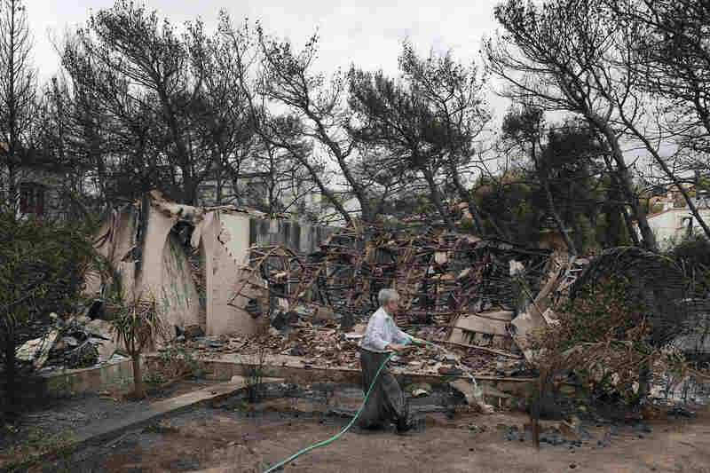 A woman sprays water outside her house, which was damaged by wildfires near the village of Neos Voutzas, on Tuesday.