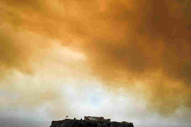 A picture taken Monday shows the Parthenon temple on the Acropolis hill in Athens as smoke from a wildfire in Kineta billows in the background.