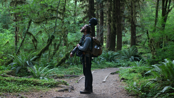 """Matt Mikkelsen carries """"Fritz,"""" his microphone system, to the path in the Hoh Rain Forest that leads to One Square Inch of Silence in Washington"""