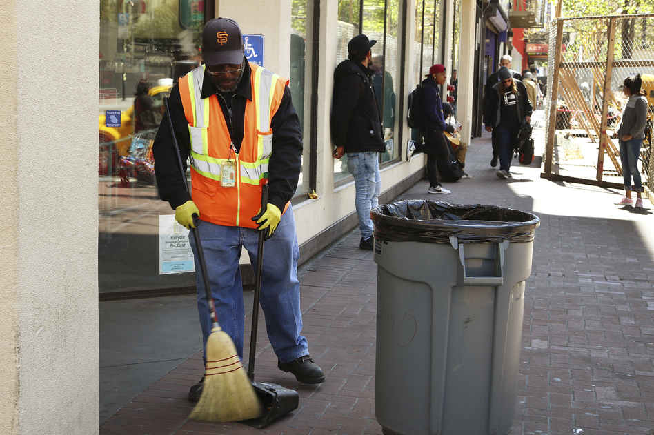 A city sanitation worker gets to work in downtown San Francisco, which says it is expecting its street cleaning budget to be more than $70 million this coming fiscal year. (Ben Margot/AP)