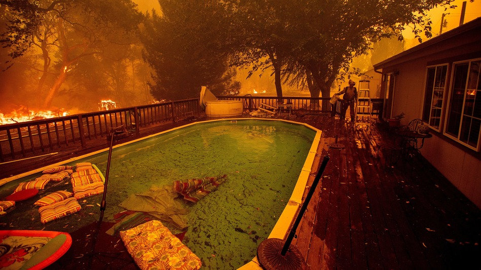 A firefighter gathers water from a pool while battling the Ranch Fire near Clearlake Oaks, Calif., on Saturday. (Noah Berger/AFP/Getty Images)