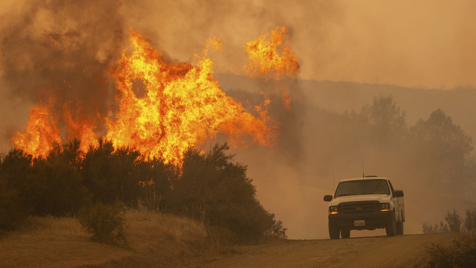 A truck passes by flames from the Ranch Fire in Clearlake Oaks, Calif., on Sunday. (Josh Edelson/AP)
