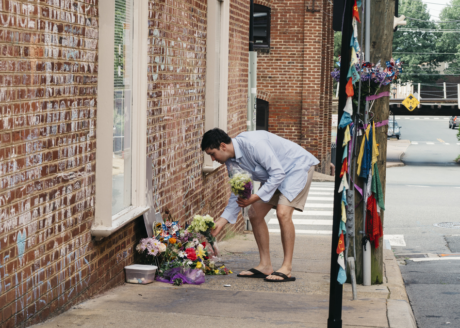 Peter Reijmers, 29, of Charlottesville, lays flowers at a memorial on 4th Street SE where Heather Heyer was killed last August. (Justin T. Gellerson for NPR)