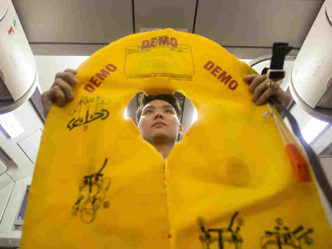 A flight attendant holds an inflatable life vest during a safety presentation on board a VietJet Air aircraft.