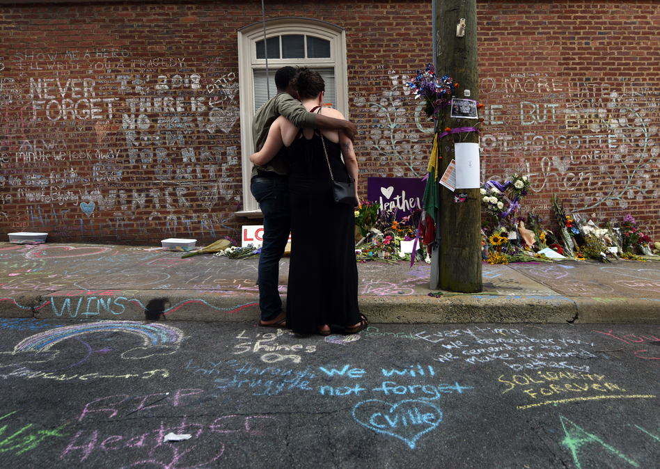 """Lindsey Reisser, 25, and her fiance Carl Thomas, 25, bring flowers to the site her friend Heather Heyer died last year at the Unite the Right rally. """"Heather was a very close friend of mine,"""" she said weeping. """"I asked her not to go. It didn't feel right, there was tension in Charlottesville."""" (Carol Guzy for NPR)"""