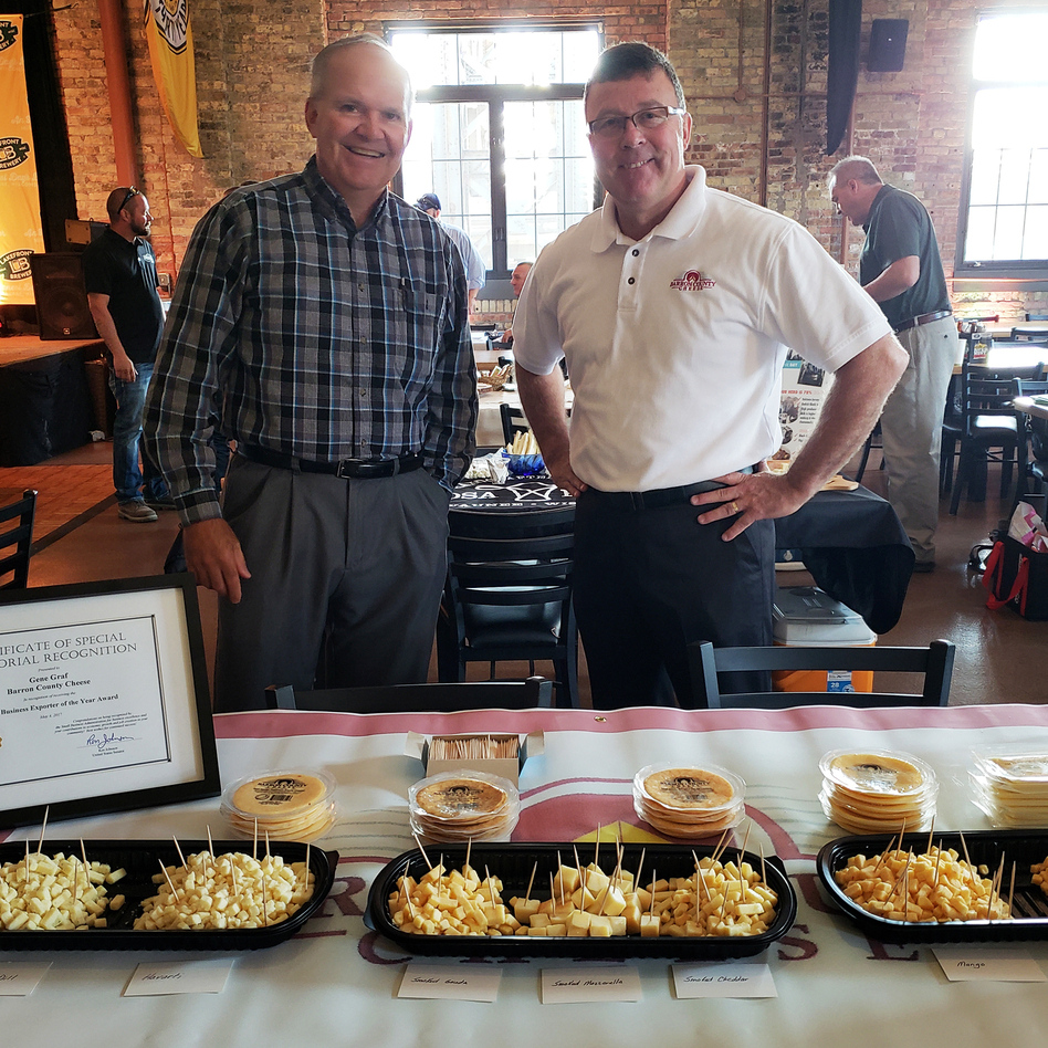 Gene Graf (right) and David Kochendorfer (left) of Barron County Cheese behind their cheese table at a Wisconsin event promoting cheese for export. (Maayan Silver/Milwaukee Public Radio)