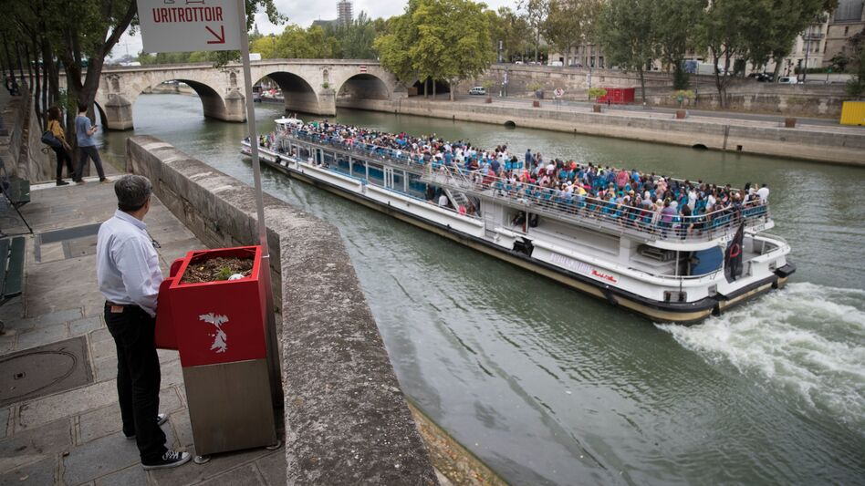 A man stands at a Uritrottoir public urinal on the Île Saint-Louis in Paris.