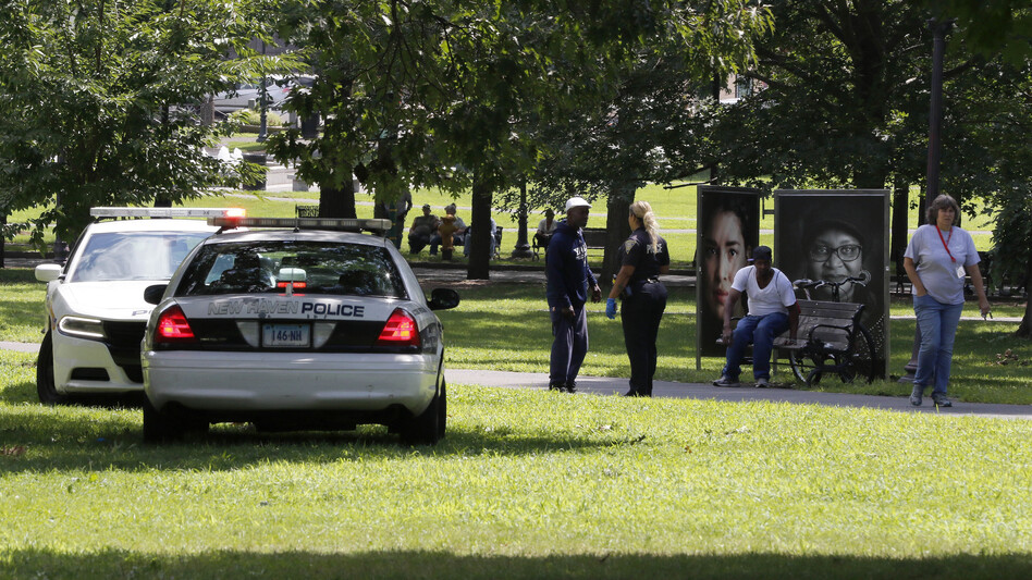 A police officer speaks to a man on New Haven Green, where more than 70 people fell ill from suspected drug overdoses on Wednesday in New Haven, Conn. (Bill Sikes/AP)