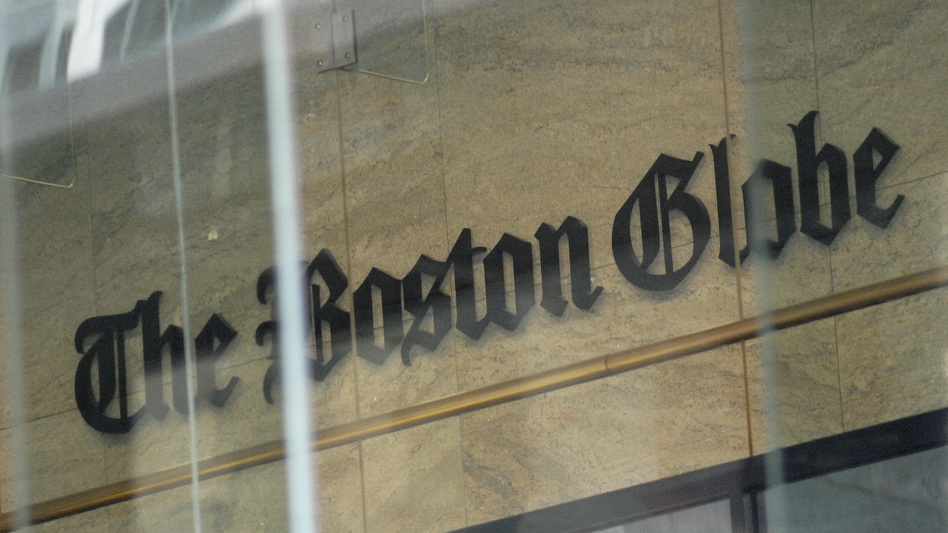 <em>The Boston Globe</em>'s logo as seen through the windows across from the new location of the <em>Globe</em> in Boston. The paper's editors coordinated a campaign defending a free press in editorials. (Joseph Prezioso/AFP/Getty Images)
