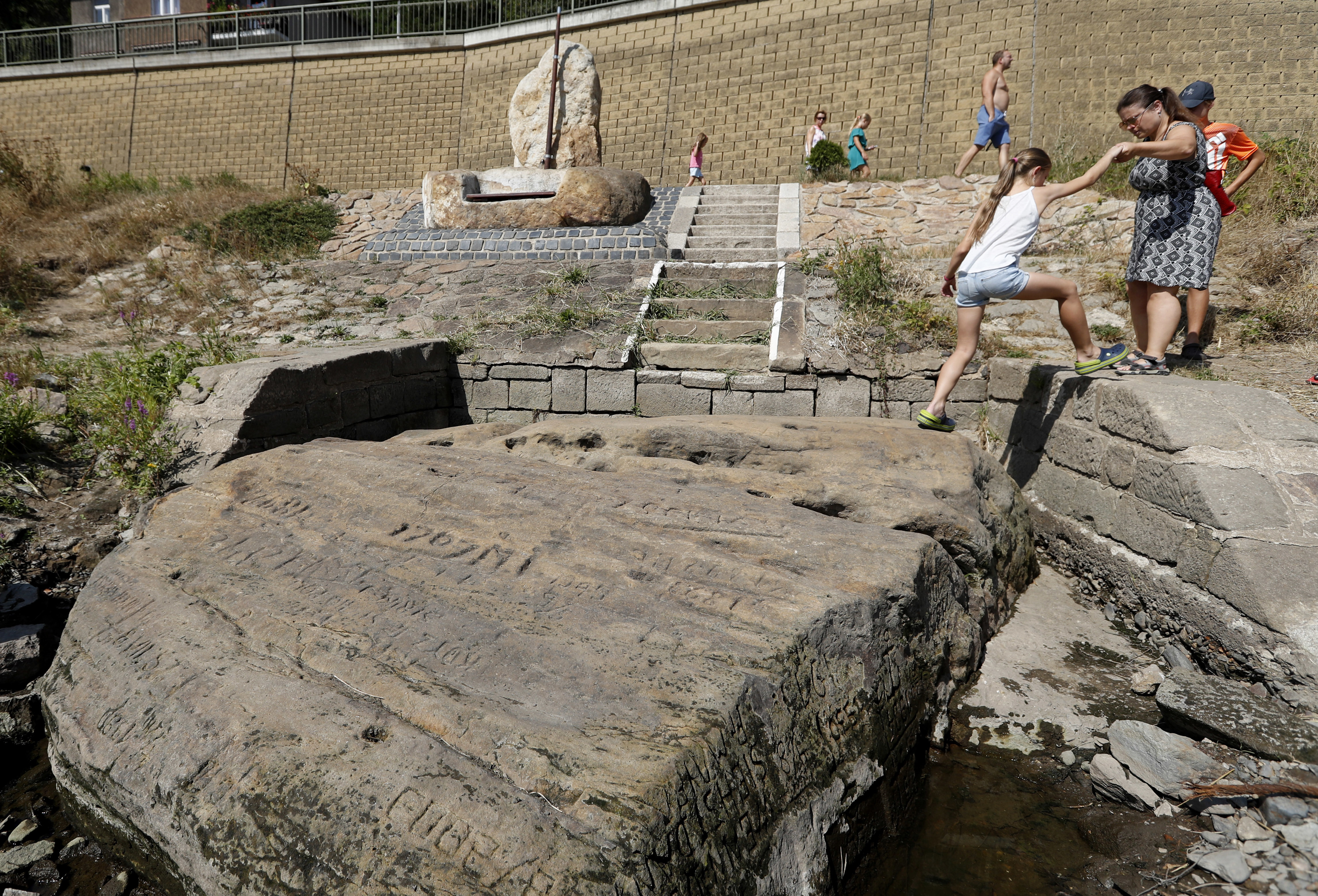 """People visit a famous """"hunger stone"""" exposed by the low level of water in the Elbe river in Decin, Czech Republic, on Thursday."""