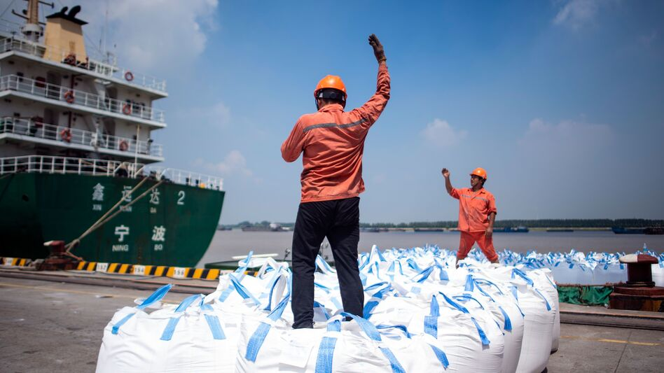 Dock workers unload bags of chemicals earlier this month at a port in Zhangjiagang, north of Shanghai. (Johannes Eisele/AFP/Getty Images)