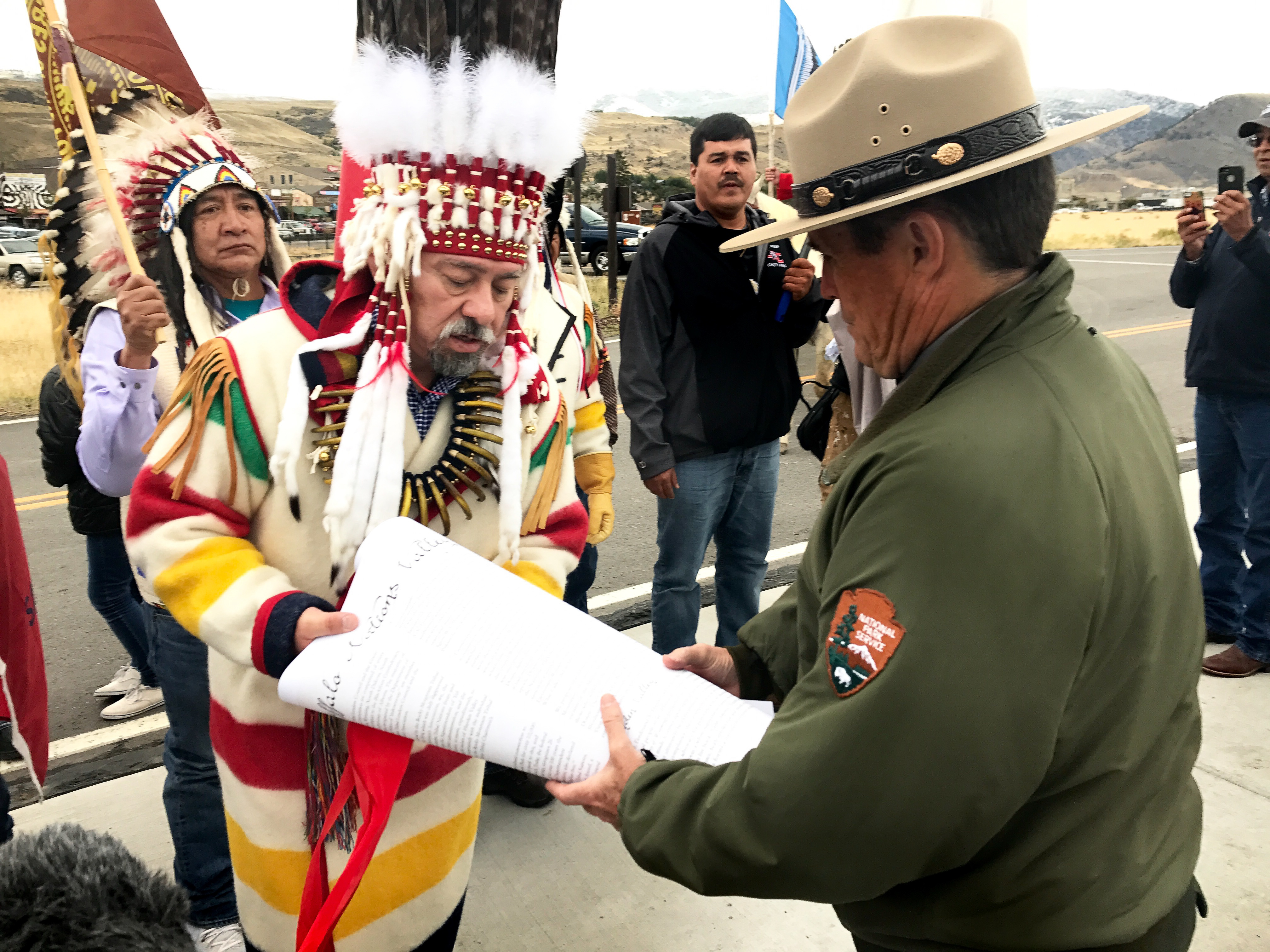 Chief Stanley Charles Grier of the Piikani Nation hands over a declaration to Yellowstone National Park deputy superintendent Pat Kenney.