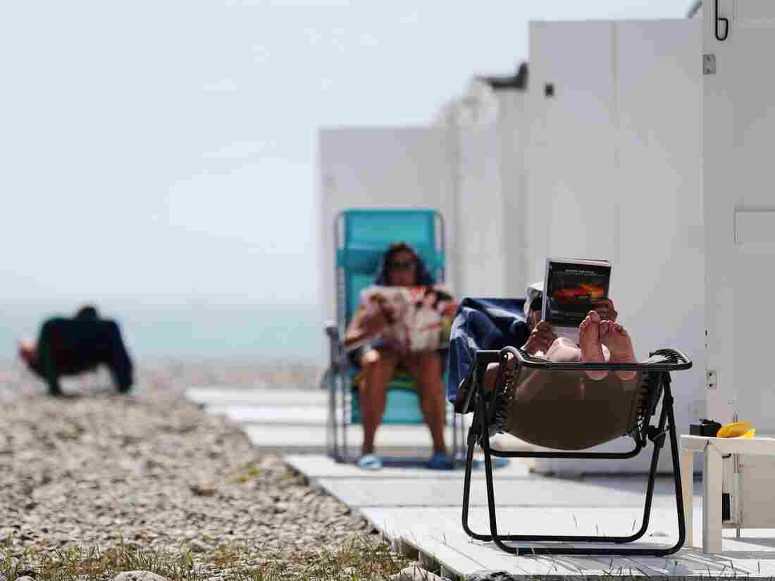 People sit reading on the beach on a sunny day in Le Havre, northwestern France, on May 27, 2016. / AFP / CHARLY TRIBALLEAU (Photo credit should read CHARLY TRIBALLEAU/AFP/Getty Images)