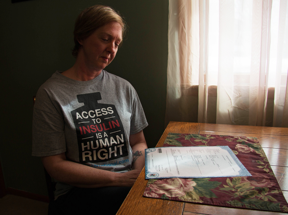 """It shouldn't have happened,"" says Nicole Smith-Holt of Richfield, Minn., gazing at the death certificate of her son Alec Raeshawn Smith. (Bram Sable-Smith for NPR)"