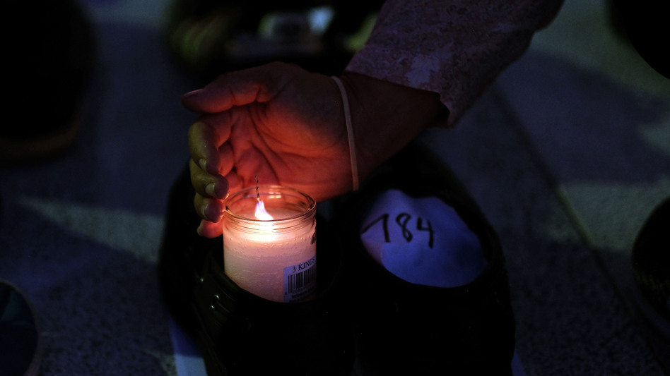 A woman lights a candle inside a pair of shoes that were among hundreds displayed in memory of those killed by Hurricane Maria in front of the Puerto Rican Capitol, in San Juan in June. (Ricardo Arduengo/AFP/Getty Images)
