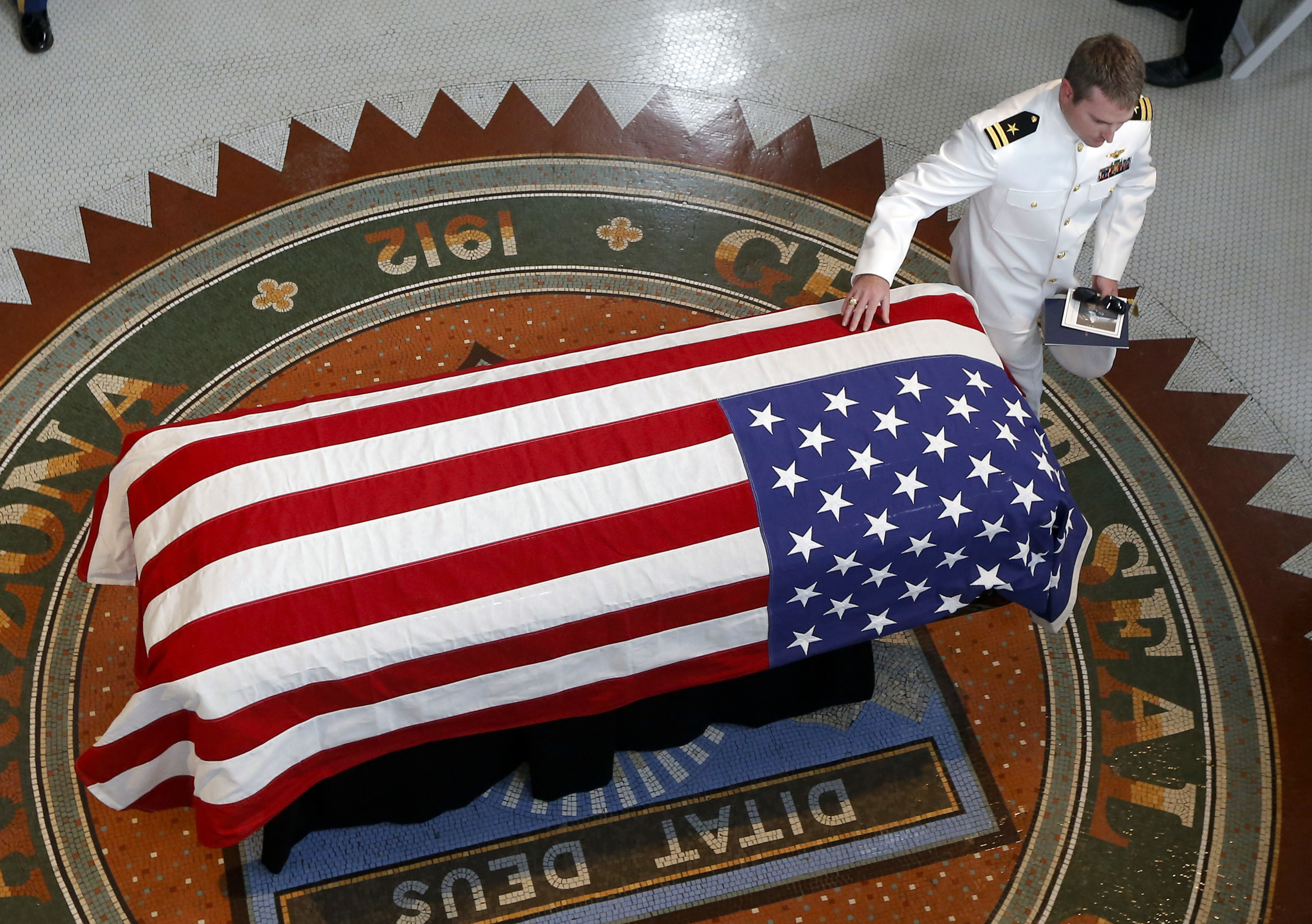 Jack McCain son of Sen. John McCain R-Ariz. touches his father's casket during a memorial service at the Arizona Capitol on Wednesday in Phoenix