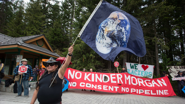 A demonstrator holds a flag with an image of Earth during a protest against the Kinder Morgan Canada Ltd. Trans Mountain pipeline expansion on June 2. On Thursday a Federal Court of Appeal ruled to stop the expansion projects indefinitely.