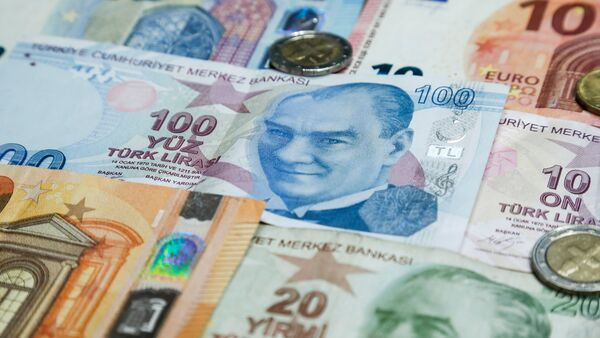 A pile of Turkish lira and euro banknotes sit atop a table earlier this month. The currencies of Turkey and other emerging economies have been falling against the U.S. dollar, which has been boosted by rising interest rates.