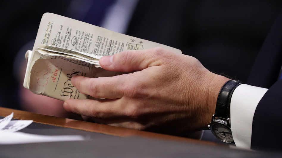 Supreme Court nominee Judge Brett Kavanaugh thumbs through a well-worn, pocket-sized copy of the U.S. Constitution as he testifies before the Senate Judiciary Committee on the second day of his confirmation hearings Wednesday. (Chip Somodevilla/Getty Images)