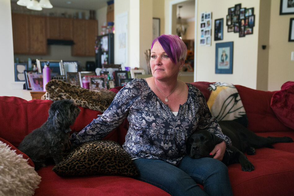 Michel, joined on the couch by longtime pet Blade and service dog Lizzy, says at least three male service members assaulted or molested her between 1990 and 2005. (Claire Harbage/NPR)