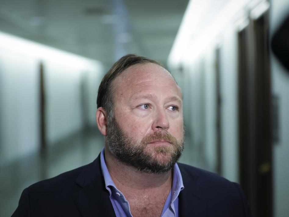 Alex Jones of InfoWars talks to reporters outside a Senate Intelligence Committee hearing on Wednesday. Twitter has permanently suspended the conspiracy theorist, citing violations of its policy on abusive behavior. (Drew Angerer/Getty Images)