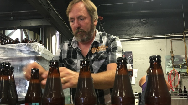 Double Mountain Brewery founder Matt Swihart grabs freshly bottled pale ale from the bottling line in Hood River. The ale is among the first to be sold in Oregon