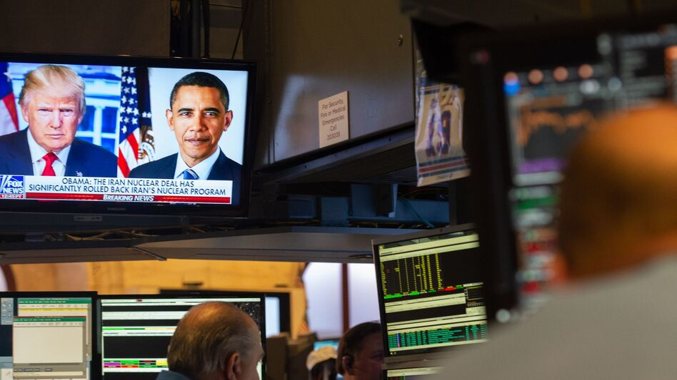 Images of President Trump and former President Barack Obama are on television as traders work on the floor of the New York Stock Exchange. (Bryan R. Smith/AFP/Getty Images)