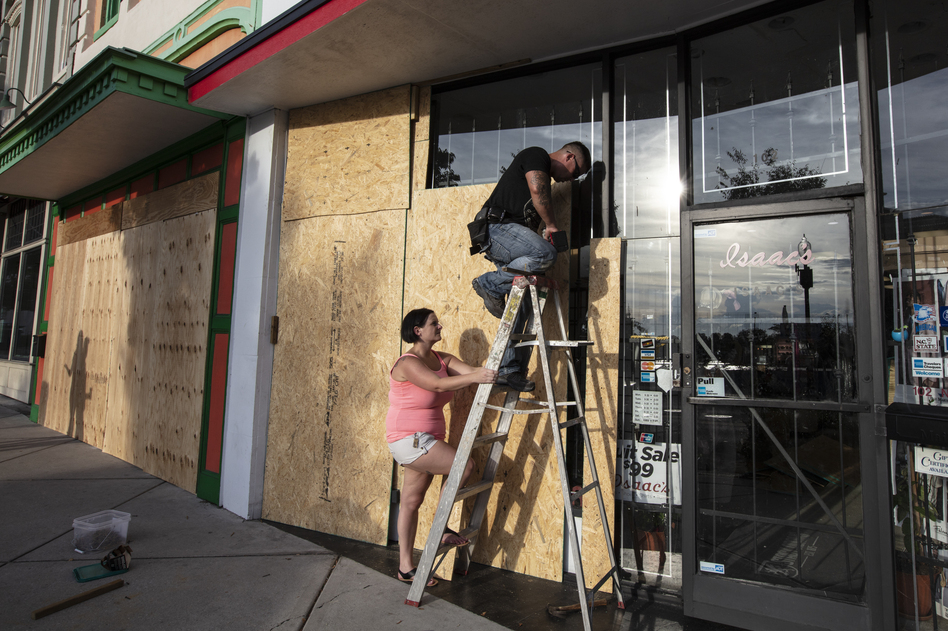 Jacob Harrelson and his wife, Beth, install protective plywood on a local business in anticipation of Hurricane Florence in Wilmington, N.C., on Wednesday.
