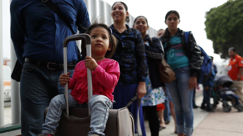 Asylum seekers line up at the San Ysidro port of entry in Tijuana, Mexico. The ACLU announced today a preliminary agreement with the Trump administration to allow some parents already in the U.S. but separated from their children at the border to apply for asylum.